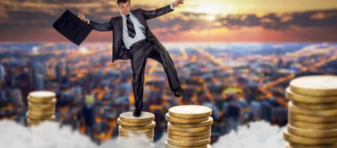 Businessman jumping on stacks of coins. Fragile unstable business, bankruptcy risk, financial balance