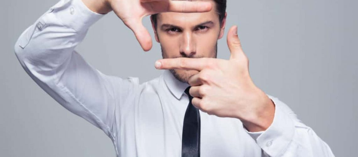 Businessman making frame gesture over gray background and looking at camera